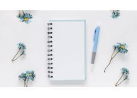蓝色洋甘菊花边的记事本和钢笔_5471506