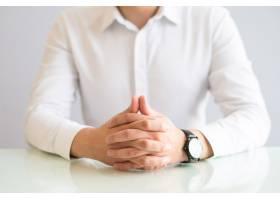 男人紧扣双手坐在餐桌旁的特写_3581169
