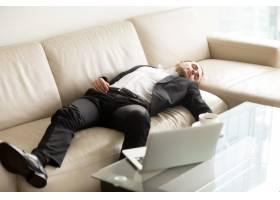 疲惫的商人睡在办公室的沙发上_4013379
