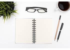 白色书桌上打开的螺旋空白笔记本_1147892