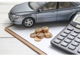 白色桌子上的车模计算器和硬币_1192518