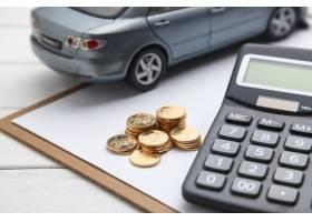 白色桌子上的车模计算器和硬币_1192712