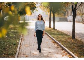 秋天公园里穿着蓝色毛衣的年轻女子_3389558