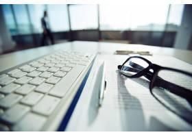 桌子上的键盘和眼镜的特写_862930