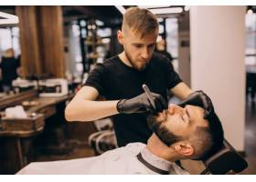 理发店的一名男子正在理发和修剪胡须_7435495
