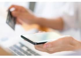 手持信用卡使用笔记本电脑和手机进行网上_1254915