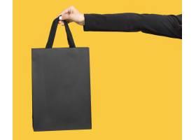 手持大黑色购物袋复印空间的人_10419036