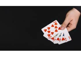 扑克玩家的手黑色背景上有皇家同花心_3422696