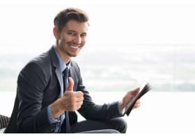 微笑的年轻商人竖起大拇指举着平板电脑_999520