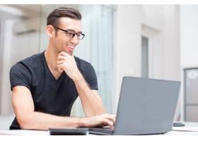 快乐的年轻帅哥在笔记本电脑上工作_1304815
