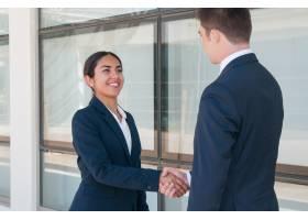 微笑的雄心勃勃的女商人与合作伙伴告别_4999709
