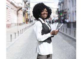 微笑的非洲年轻女商人站在城市道路上拿着_4767818