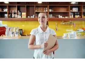 心满意足的女人拿着剪贴板经营咖啡店生意_6765776
