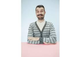 快乐而微笑的商人坐在蓝色演播室背景下的餐_13455872