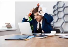 愤怒的年轻商人看着笔记本电脑办公室背景_7855238