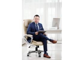 成功的亚洲企业高管在宽敞的办公室里盘腿坐_5699202