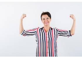 成熟的女人穿着条纹衬衫展示肌肉看起来自_13401853