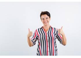 成熟的女人竖起双拇指穿着条纹上衣微笑_13401909