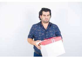成熟的男人拿着礼品盒穿着衬衫看向别处_13463927