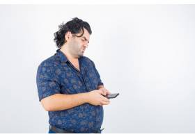 成熟的男人穿着衬衫看着手机看起来若有所_13463974