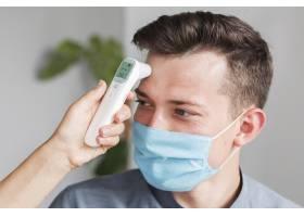 戴医用口罩的男子用温度计在办公室测体温_10070667