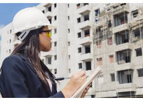 戴安全帽的非洲裔美国女士在在建建筑附近的_3724293