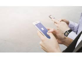 戴着智能手表的女子在移动设备上使用Facebo_2611210