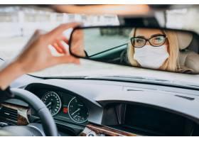 戴着防护面罩的女商人坐在车里_7869694
