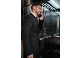 年轻商人在酒店电梯里打电话的肖像商务旅_10104157