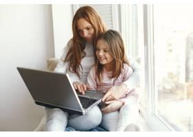 带着女儿的妇女使用笔记本电脑_9659267