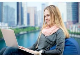 年轻女孩拿着笔记本电脑坐着背景是城市风_1280680