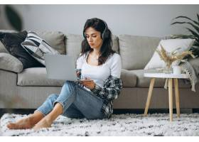 年轻漂亮的女人坐在家里戴着耳机在笔记本上_7375278