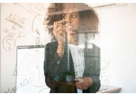 年轻漂亮的女商人在玻璃板上写字自信经_9650620