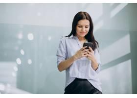 年轻的女商人在办公室使用电话_6640078