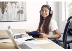 年轻的学生坐在桌子旁使用笔记本电脑_5913129