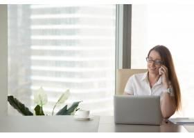 年轻的微笑女商人在工作场所打电话移动通_3938521