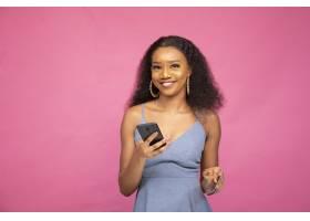 年轻的非洲女性使用她的智能手机和信用卡在_13006856