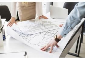 建筑师工程师在谈判桌上讨论蓝图_2593021