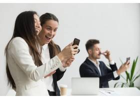 形形色色的女同事在办公室里笑着玩智能手机_3952621
