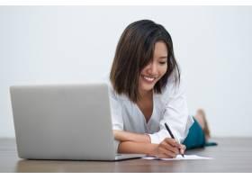 微笑的亚洲妇女用笔记本电脑在地板上写字_992990