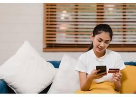 微笑的亚洲年轻女子使用智能手机网购_4691881
