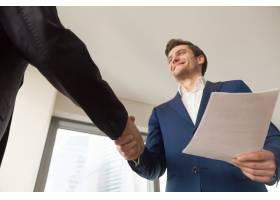 微笑的公司经理在办公室欢迎客户_3955607