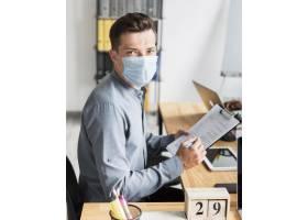 大流行期间一名戴口罩的男子在办公室工作_10070543