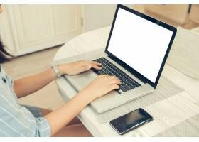 女性坐在打开的笔记本电脑和智能手机前空_1381329