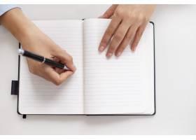 女性手在桌上笔记本上写字的俯视图_3298036
