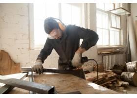 小工人在车间内磨削钢金属异型材_1282168