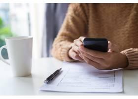 商务女士在检查文件时使用小工具的特写_3798984