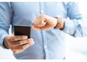 商务人士拿着智能手机查看时间的特写_3628586