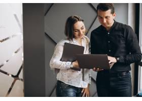 商界女性和商界男性同事在笔记本电脑上工作_8828038