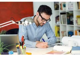 在办公室工作的英俊的年轻商人_1139690